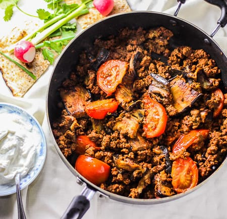 photo of gheimeh bademjan (persian seared eggplant with tomato beef) in a pan on a white tablecloth. Next to the pan is some garlic yogurt in a small plate and some Persian herbs and Persian bread.