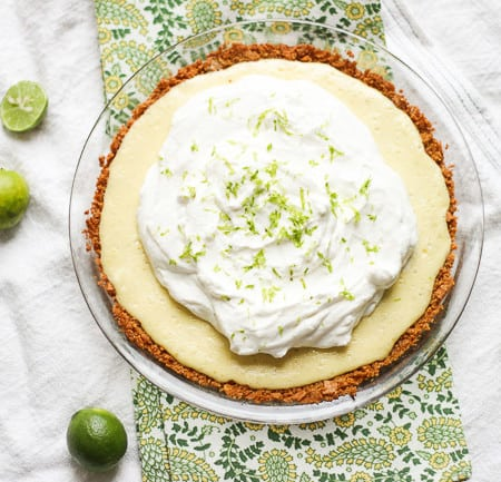 this is a key lime pie from above and it's covered in whipped cream. It's sitting in a clear, glass pie dish atop green and white tablecloths.