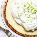 This is an up-close shot of key lime pie from above. The pie takes up most of the screen and the pie has loads of whipped cream and some fresh lime zest on top.