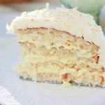 This is a photo of a slice of coconut cake. There are four layers with coconut pastry cream between them. The frosting is white with toasted flaked coconut on top.