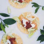 photo of three baja fish tacos on white tablecloth, surrounded by some citrus leaves and limes. Tacos have fist, crema, salsa, and cabbage on top of open tortillas.