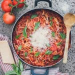 shot of best one-pot pasta from above. Pasta is red with green basil and parmesan strewn on top. There is a wooden spoon on top of the pan, a red and white napkin, and some ingredients strewn about around the pan.