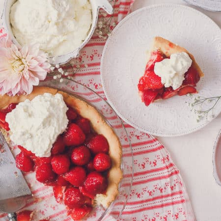 photo of fresh strawberry pie slice next to rest of pie, topped with whipped cream. there is a pink dahlia flower and a red and white table cloth.