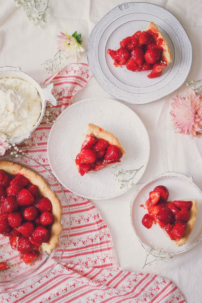 top view of three slices of fresh strawberry pie with easy crust and some cream and rest of pie partly in shot