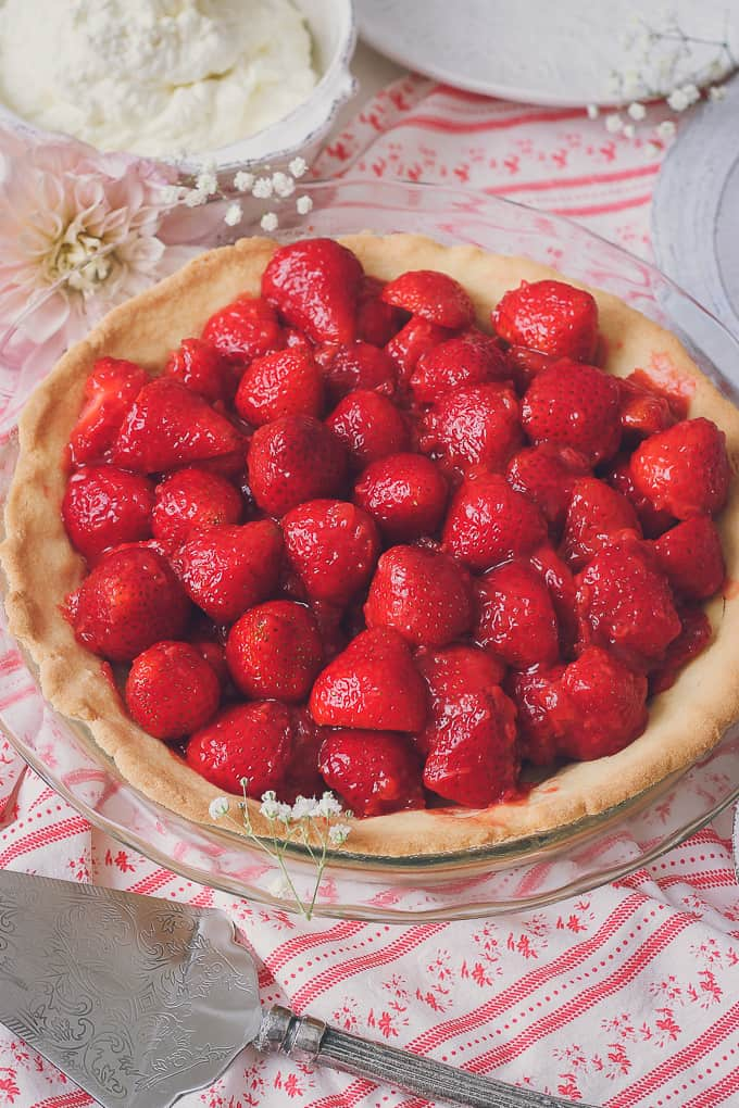 angled view of full strawberry pie with shortbread crust in pie dish