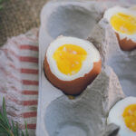This is a photo focused on 1 of 3 hard-boiled eggs sitting in a cardboard egg carton, on top of a striped red and cream napkin. The eggs are shot from 45 degrees and shows their set yolks and set whites.