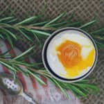 This is a photo of a soft-boiled egg shot from above. It's sitting in a small egg holder and the yolk is bright orange and jammy/runny and golden, with a set egg white surrounding it.
