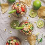 photo of three glasses filled to the brim with ceviche. there is lime, flowers, and chips decorating the shot.