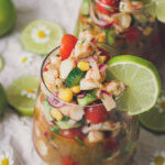 photo of shrimp ceviche in glasses, overflowing and colorful with limes and flowers to decorate