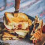 Image of stack of brie grilled cheese sandwiches with fig jam and apples. There's a cheese knife stuck into the top sandwich. There's another sandwich sitting upright next to the stack.
