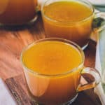 This is a photo of three glasses filled with the best, golden and rich bone broth. Photo is from 45 degrees and glasses are sitting on a wooden surface.