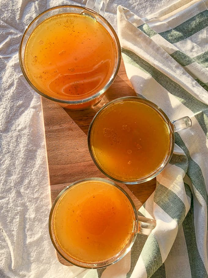 top view of 3 glasses of simple bone broth sitting on a wooden board with tablecloths strewn around them