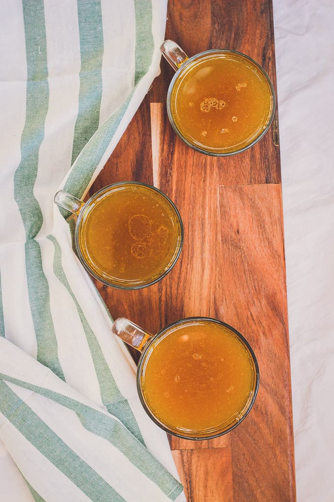 vertical image of three filled glasses with nutritious bone broth