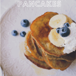 Photo shows stack of pancakes from a 60 degree angle. They're topped with whipped cream, blueberries, and banana slices and the stack is on a white plate.