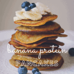 Pancake stack is shown from the side, sitting on a white plate and topped with whipped cream, banana slices, and blueberries.
